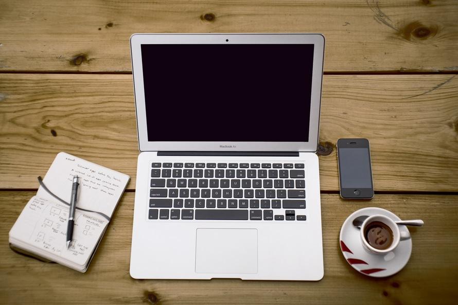 Un ordinateur, un bloc ouvert, un téléphone et un café pour symboliser une séance de travail sur le web.